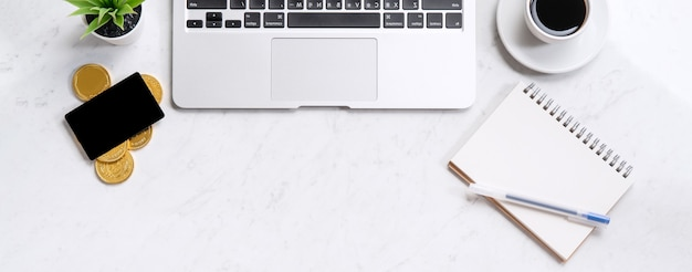 Biznesowa koncepcja projektu finansowego, marmurowy biały stół biurowy widok z góry ze smartfonem, makieta karty kredytowej, monety, laptop, układanie na płasko, miejsce na kopię