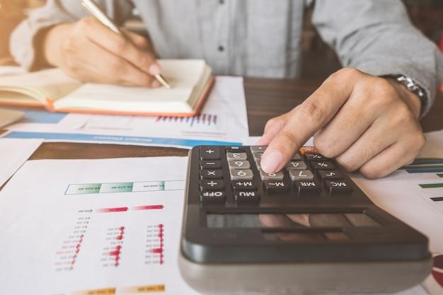 Biznesowa księgowość, biznesmen używa kalkulatora z budżeta dokumentem, pióro