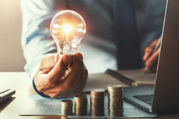 Biznesowa księgowość z oszczędzanie pieniądze z ręki mienia lightbulb pojęciem pieniężnym