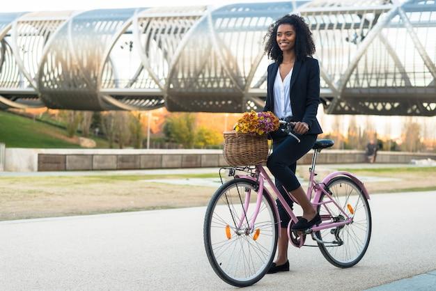 Biznesowa murzynka jedzie rocznika bicykl w mieście