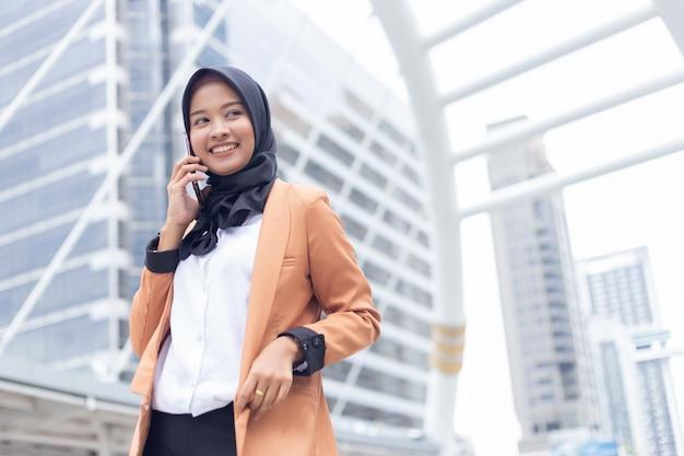 Biznesowa muzułmańska kobieta używa telefon w mieście.