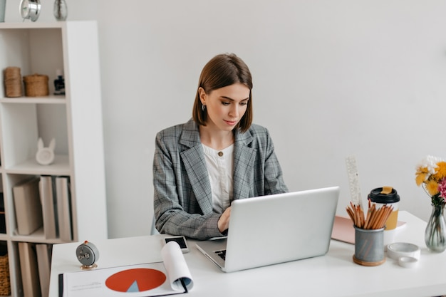Biznesowa pani w szarej kurtce pracuje w laptopie. portret kobiety w biurze.