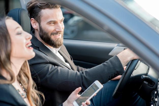 Biznesowa para prowadzi zabawną rozmowę podczas jazdy samochodem w mieście