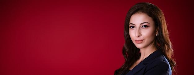 Biznesowa piękna kobieta w garniturze pozuje na czerwonym tle