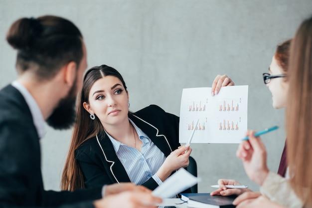 Biznesowa praca zespołowa. koledzy analizujący dane. lider wskazujący na statystyki.
