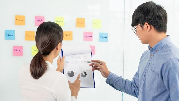 Biznesowa praca zespołowa w spotkaniu i karteczce samoprzylepnej na tablicy lustrzanej omawianie z zespołem