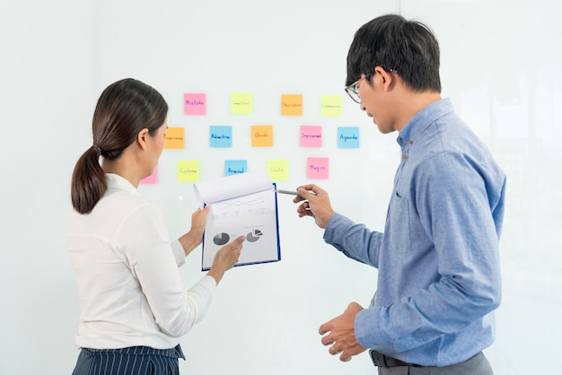 Biznesowa praca zespołowa w spotkaniu i samoprzylepna karteczka na tablicy lustrzanej dyskutowanie z zespołem w biurze w celu zebrania planu burzy mózgów.