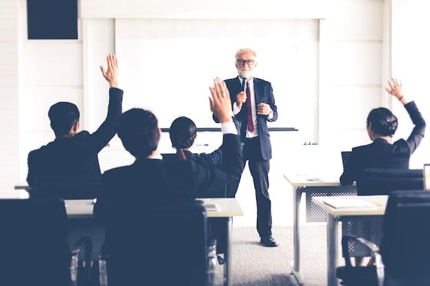 Biznesowa publiczność podnosząc rękę i mówiąc w szkoleniu o opinię w spotkaniu