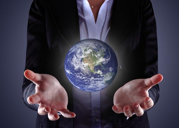 Biznesowa ręka trzyma kulę ziemską