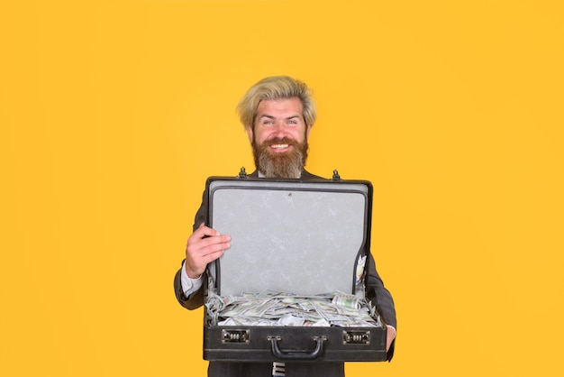 Biznesowa sprawa z dolarami uśmiechnięty biznesmen trzymaj walizkę z pieniędzmi brudny biznesmen z pieniędzy