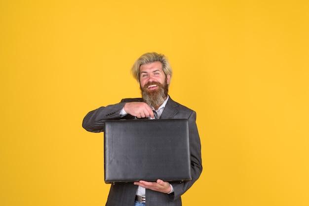 Biznesowa walizka pracownik biurowy uśmiechnięty biznesmen z walizką dyrektora brodaty biznesmen w garniturze