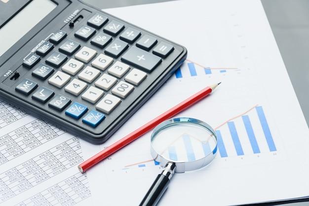 Biznesowe dokumenty finansowe, kalkulator biurowy i długopis na stole. liczby i wykresy