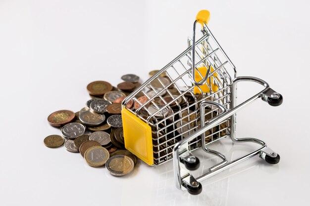Biznesowe i finansowe koncepcja zakupów z koszykiem pełnym z wieloma monetami