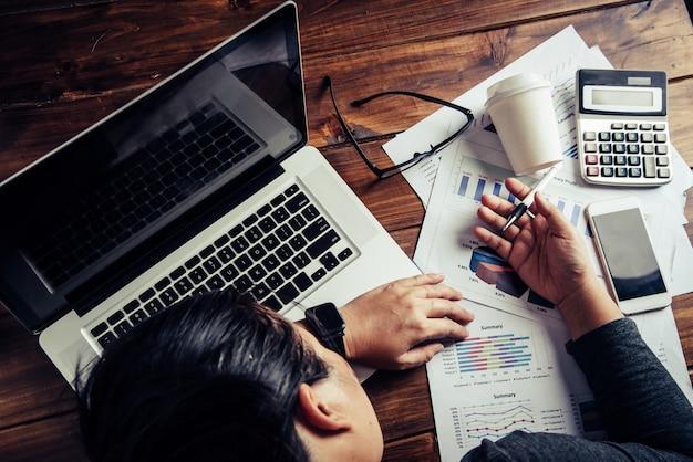 Biznesowe kobiety chore na pracę, śpią na dokumencie i komputerze.