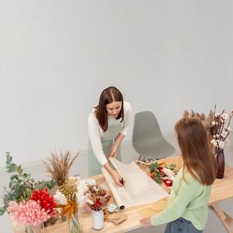 Biznesowe kobiety pracuje przy kwiatu sklepem z planami