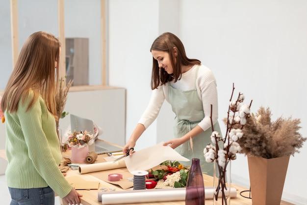 Biznesowe kobiety pracuje przy kwiatu sklepem
