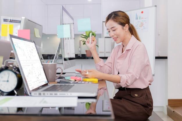 Biznesowe kobiety uśmiechnięte gospodarstwa inteligentny telefon do rozmowy z telefonem głośnomówiącym i robienia notatek pisać na biurku w biurze.