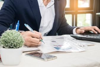 Biznesowego mężczyzna writing na notepad i działanie na laptopie w biurowym pokoju, zakończenie up.