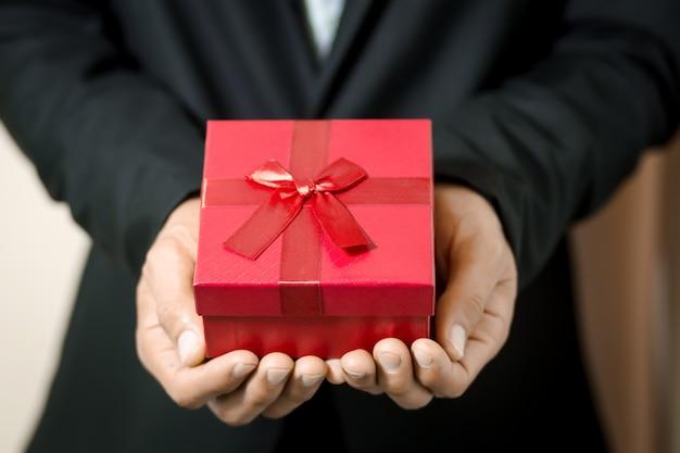 Biznesowego mężczyzna chwyta czerwony prezenta pudełko w rękach.