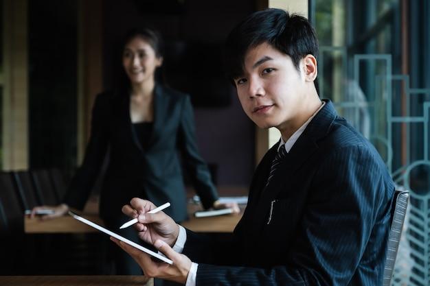 Biznesowego mężczyzna konsultant używa cyfrową pastylkę i biznesowej kobiety pracuje przy biurem. konto, finanse, koncepcja podatkowa.