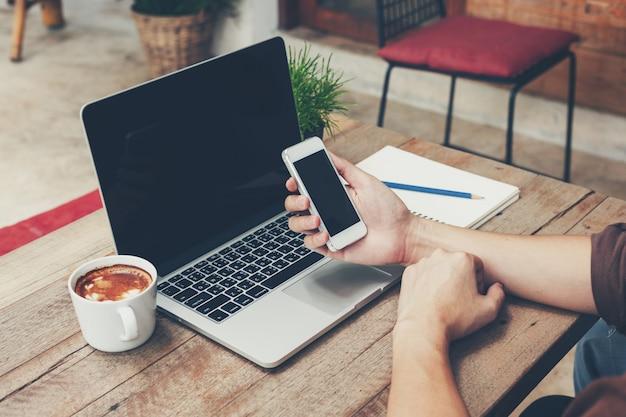 Biznesowego mężczyzna mienia telefon i laptop na drewnianym stole. vintage stonowanych.