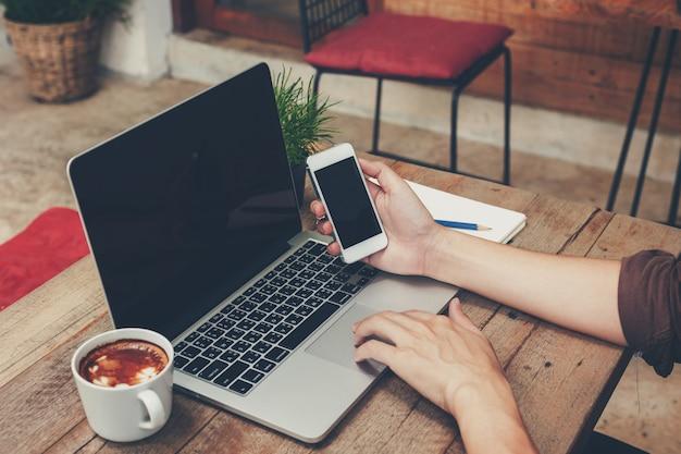 Biznesowego mężczyzna mienia telefon i używać laptop na drewnianym stole