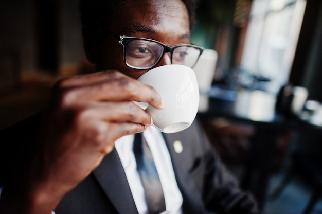 Biznesowego mężczyzna odzież na czarnym kostiumu i szkłach przy biurem, pije ranek kawę przed dniem pracy