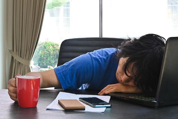 Biznesowego mężczyzna odzieży przypadkowi ubrania śpią w domu biurowym biurku z laptopem i filiżanką kawy podczas gdy pracujący od domu. pojęcie dla przepracowanego