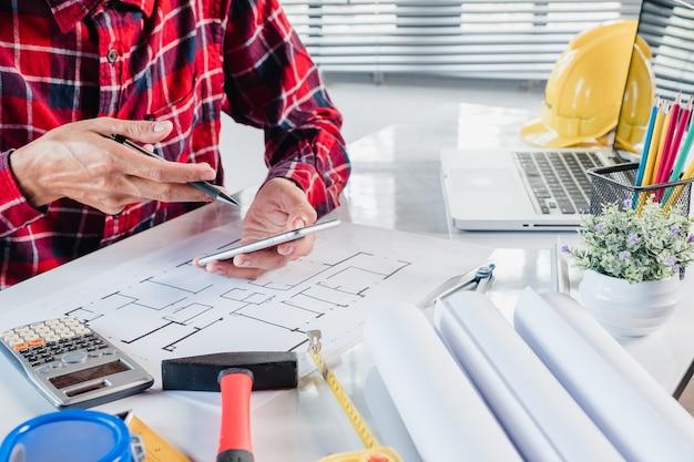 Biznesowego mężczyzna projektant wnętrz pracuje dane z mądrze telefonem i dyskutuje