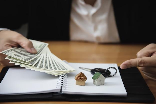 Biznesowego mężczyzna przedstawienia pieniądze banknot robi pieniężnemu planowi zaprasza ludzi sprzedawać lub kupować dom i samochód - monetarnych własności pożyczki kredyta ubezpieczenia pojęcie