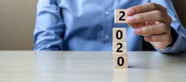 Biznesowego mężczyzna ręka trzyma drewnianego sześcian z 2020 słowem na stole
