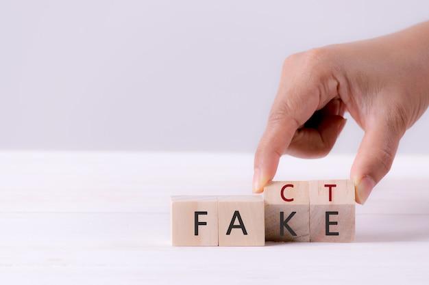 Biznesowego mężczyzna ręka trzyma drewnianego sześcian z odwraca blok fake słowo fact