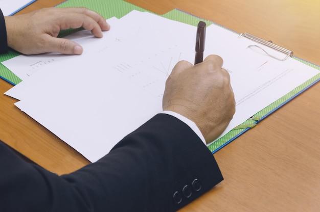 Biznesowego mężczyzna ręki podpisywanie na dokumencie