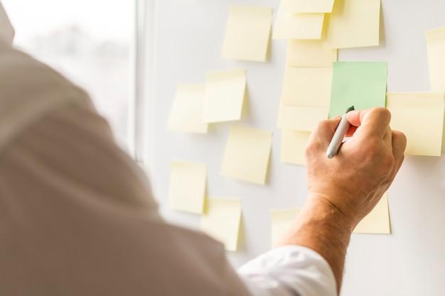 Biznesowego mężczyzna writing na nutowych papierach