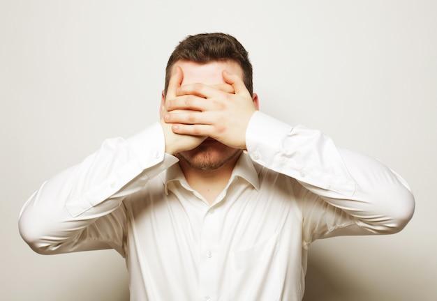 Biznesowego mężczyzna zakrywa oczy z jego rękami