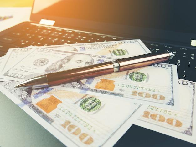 Biznesowego raportu wykres i pieniężna wykres analiza z dolarowym pieniądze i piórem na stole