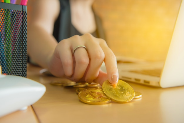 Biznesowej kobiety dotyk i przyglądający bitcoin w ręce z pić kawę w biurze