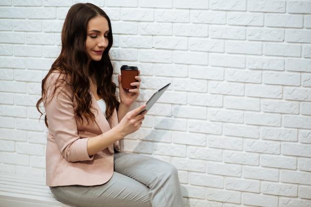 Biznesowej kobiety mienia pastylka i pić kawa