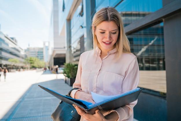 Biznesowej kobiety mienia schowek i pozycja outdoors