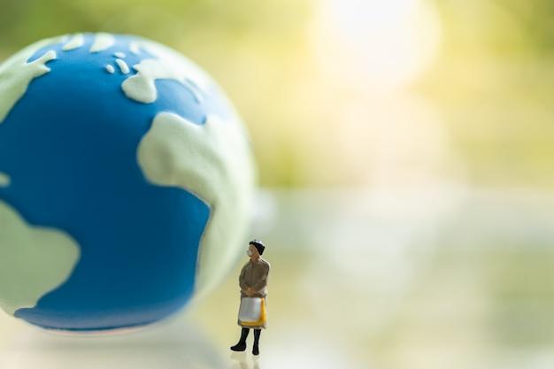 Biznesowej kobiety miniatury postaci ludzie jest ubranym maskę z torebki pozycją z mini światową piłką