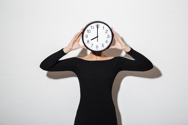Biznesowej kobiety nakrycia twarz z zegarem.
