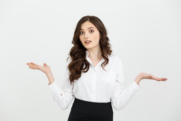 Biznesowej kobiety niespodzianka pokazuje produkt. piękna dziewczyna trzyma rękę z boku