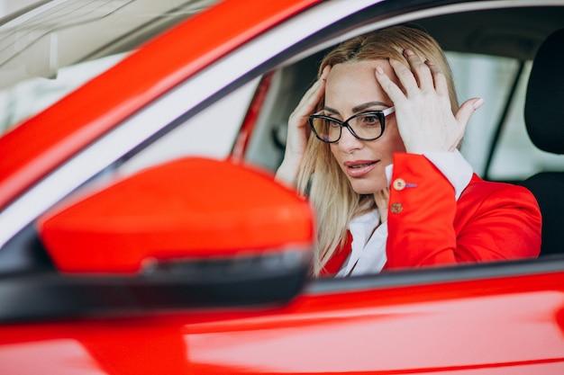 Biznesowej kobiety obsiadanie w nowym samochodzie w samochodowej sala wystawowej