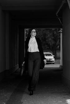 Biznesowej kobiety odprowadzenie na ulicie z okularami przeciwsłonecznymi i torebką.