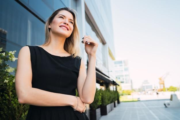 Biznesowej kobiety pozycja na zewnątrz budynków biurowych