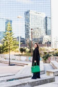 Biznesowej kobiety pozycja z zieloną torbą outside