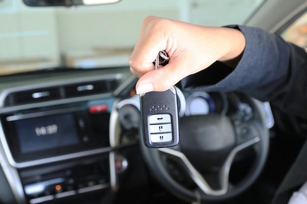 Biznesowej kobiety przedstawienia pilota klucz w nowożytnym pojazdu samochodzie.