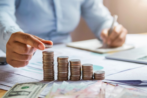 Biznesowej kobiety ręki mienia monety brogować na biurka pojęciu ratować pieniądze finanse