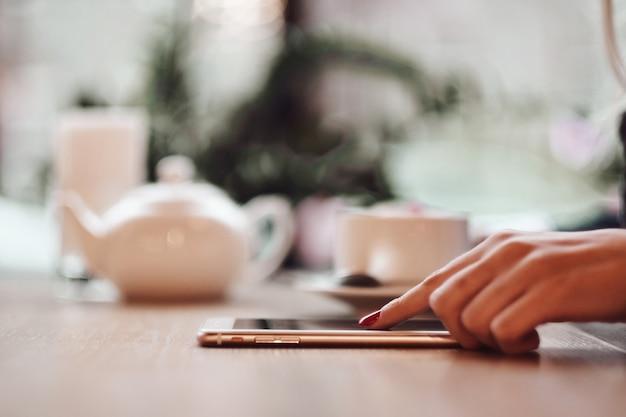 Biznesowej kobiety ręki używać mądrze telefon i filiżankę kawy.