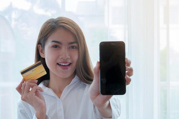 Biznesowej kobiety szczęśliwy pokazywać kredytową kartę i smatrphone płacić dla online zakupy.